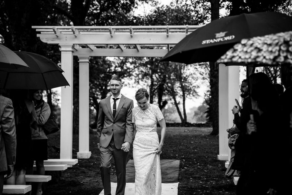 bride and groom enter outdoor rainy wedding