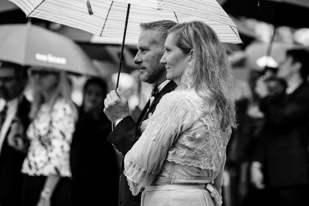 parents watch wedding under umbrella