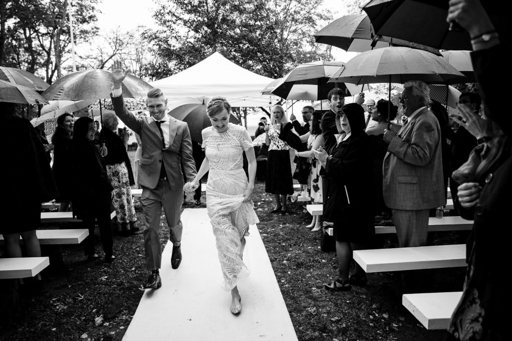 bride and groom run through the rain