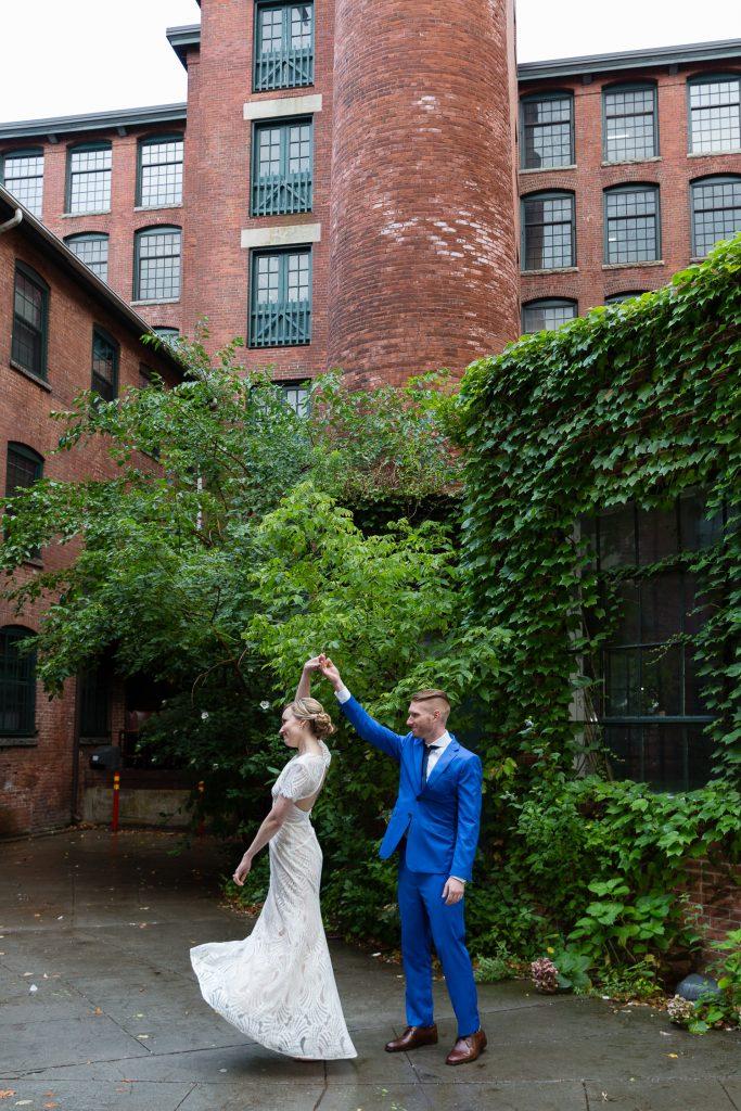 bride and groom dance in factory courtyard