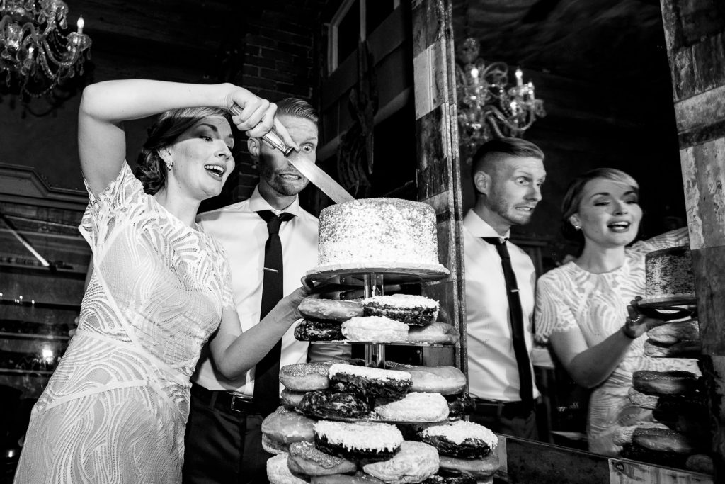 bride and groom cut cake with silly faces