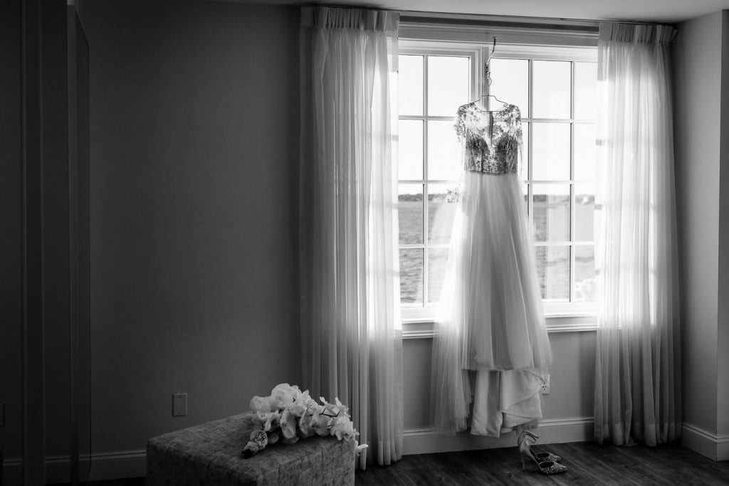 A lace wedding gown hanging in the window of the Grace Suite at Belle Mer