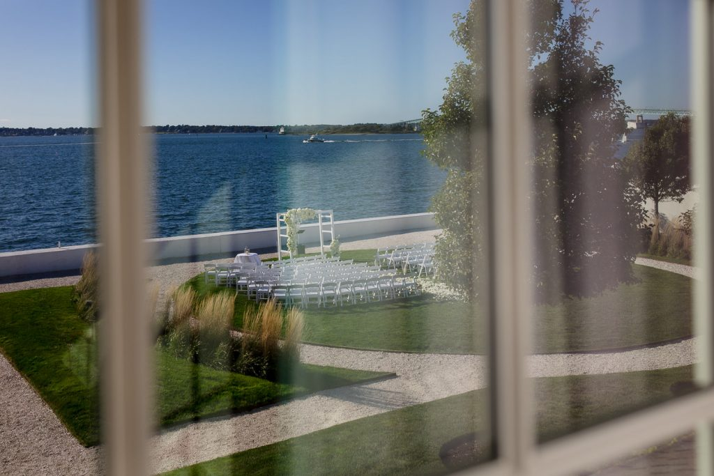A view of the lawn wedding ceremony setup through the window of the Grace suite at Belle Mer