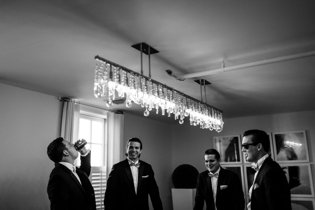 A groom and groomsmen drink and laugh in the Jackie suite at Belle Mer