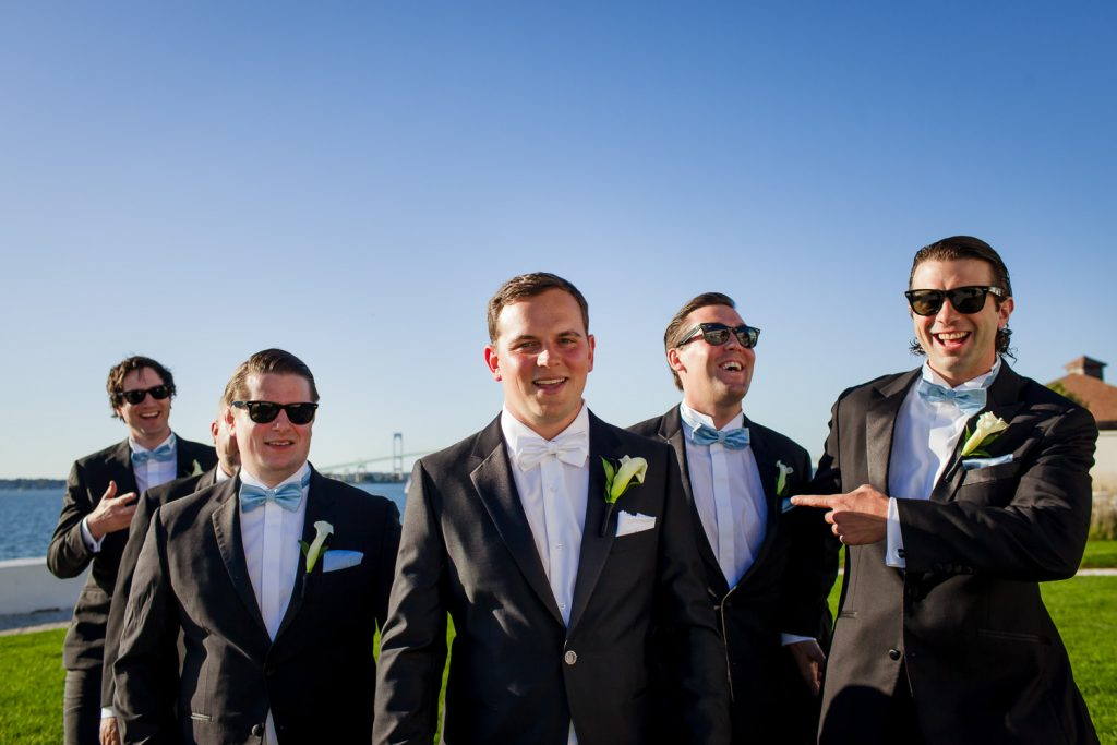 A groom and his groomsmen goof around on the lawn at Belle Mer before the wedding