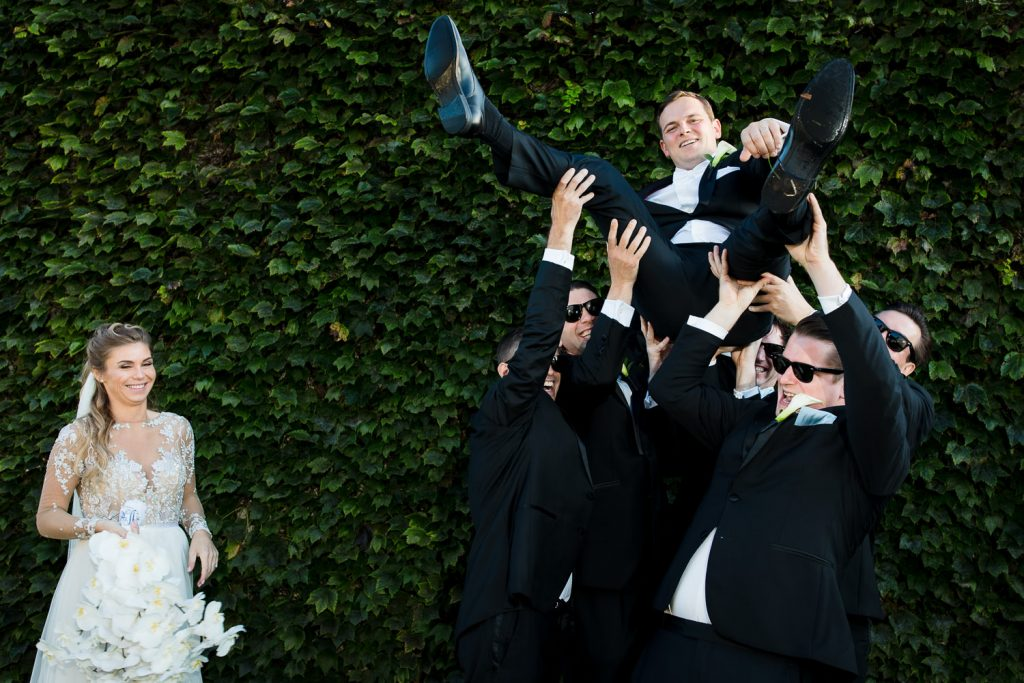 A bride watches as her groom is hoisted in the air in front of the ivy wall at Belle Mer