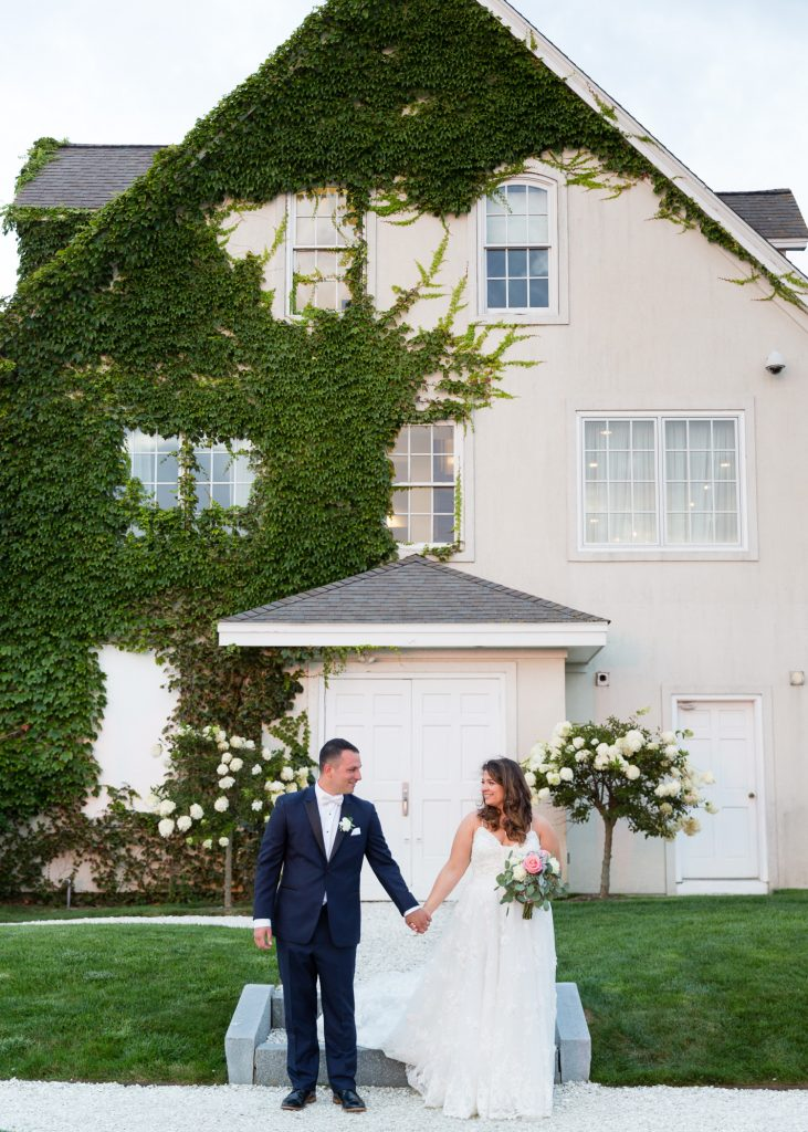 A bride and groom pose for wedding portraits in front of the ivy covered building at Belle Mer