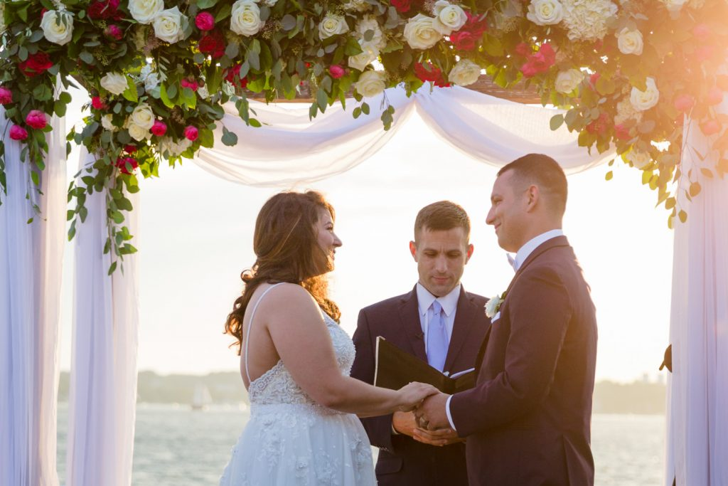 A bride and groom exchange vows at a sunset wedding ceremony by the ocean at Belle Mer