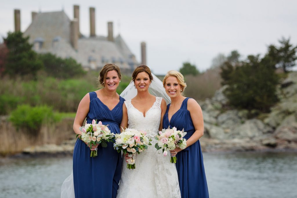 A bride poses with her bridesmaids on Cliff Walk in Newport