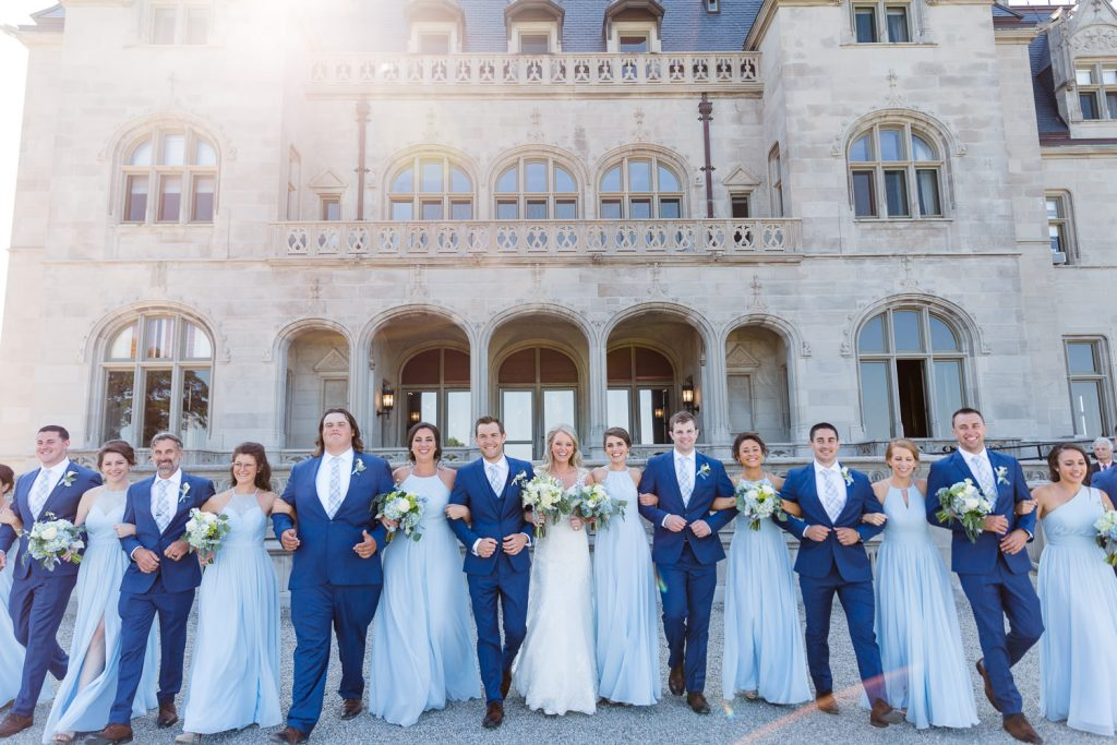 A large bridal party walk arm in arm in front of Ochre Court mansion in Newport
