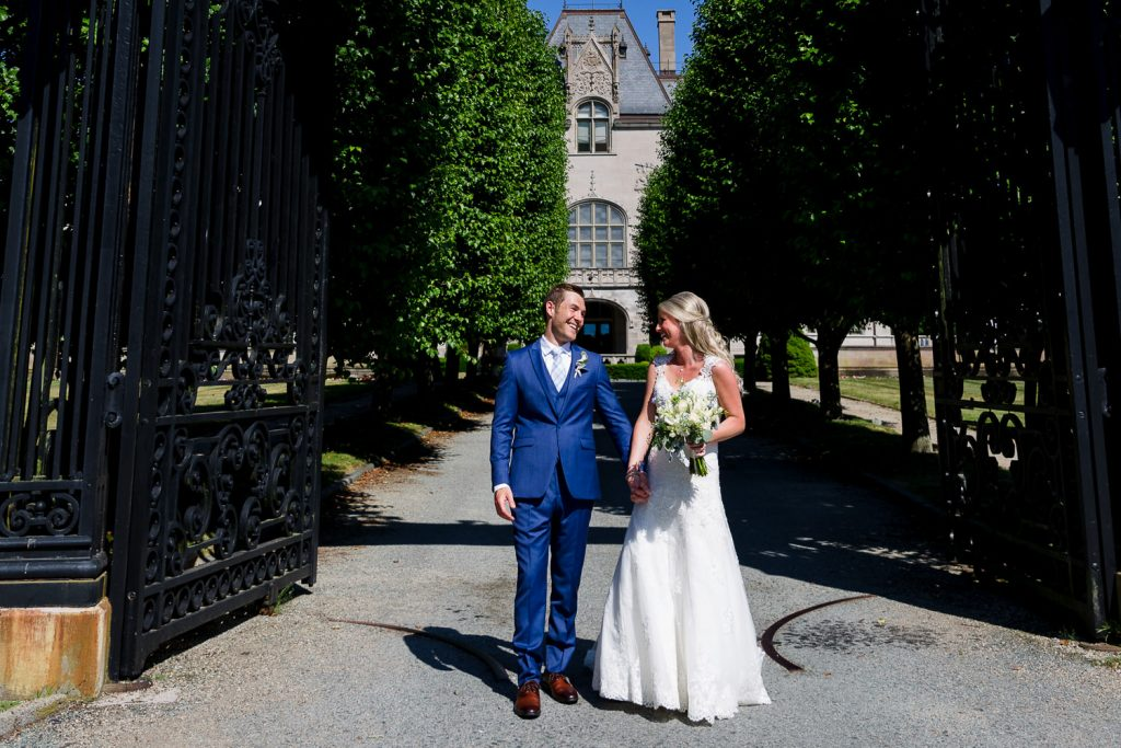 A bride and groom pose for candid wedding portraits in front of the Ochre Court mansion gates in Newport