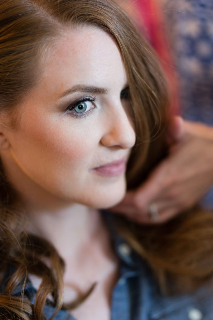 A face closeup of a redheaded blue eyed bride getting ready