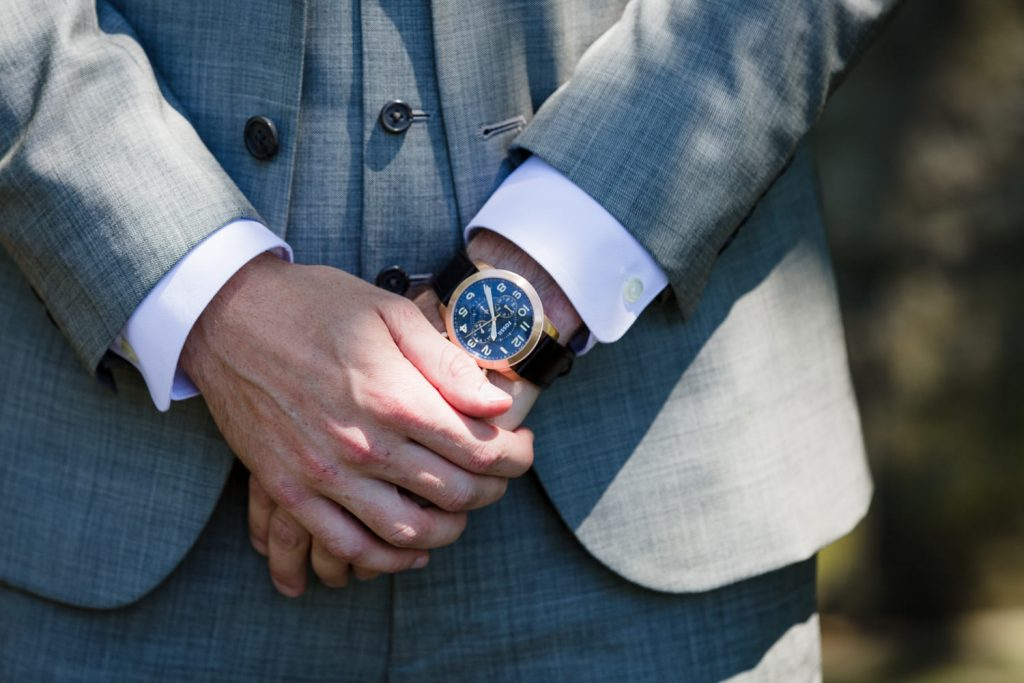 A groom in a gray suit and blue watch keeps his hands crossed in front of him