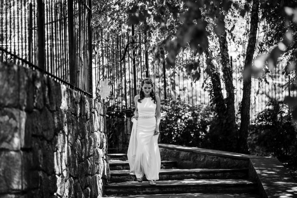 A bride walks down the stairs of conn college arboretum to a first look with her groom