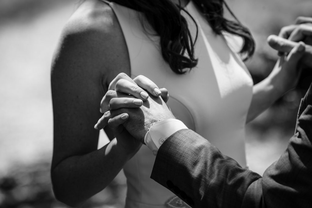 The hands of a groom entertwined with the hands of his bride