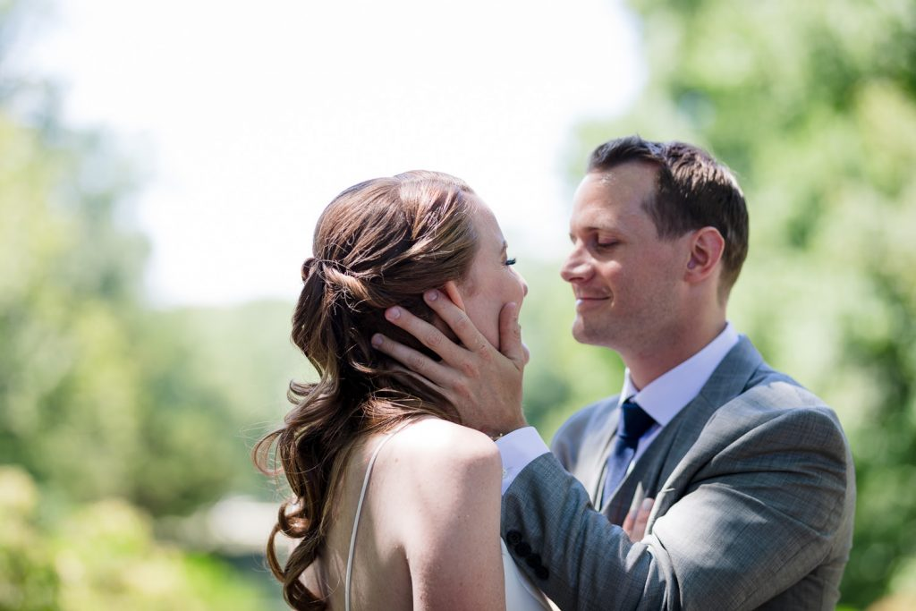 A groom holds his brides face lovingly after their wedding first look at conn college arboretum
