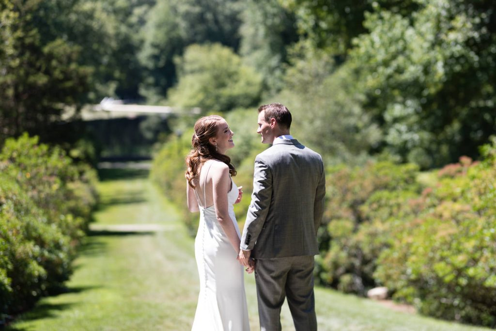 A bride and groom share a moment alone at Conn College arboretum