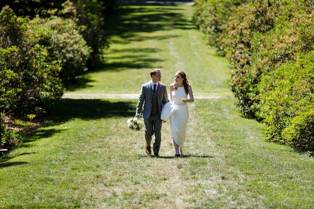 A bride and groom walk hand and hand up the hill at Conn college arboretum