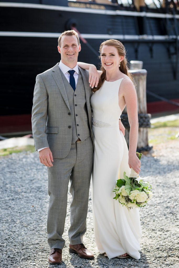 A bride and groom pose in front of a tall ship at mystic seaport