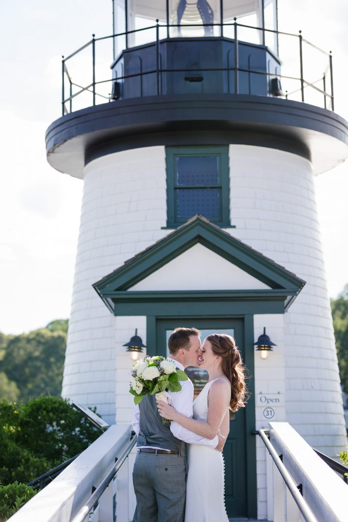 Bride and groom kiss in front of the lighthouse at mystic seaport