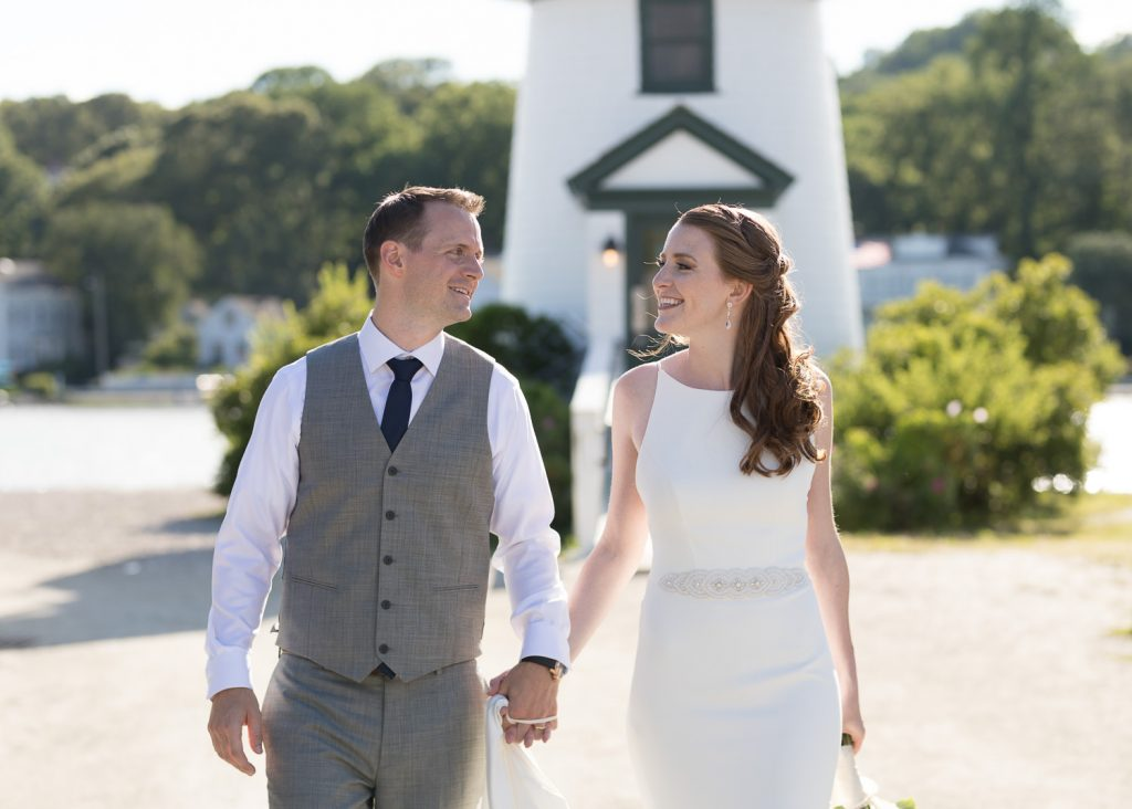 A bride and groom walk hand in hand away from the lighthouse at mystic seaport