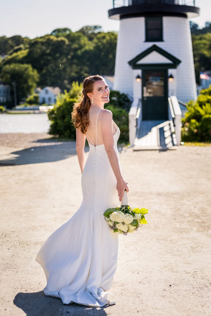 A bride poses for wedding photo in front of the mystic seaport ligthouse