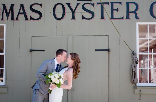 The groom dips his bride in front of the Thomas Oyster building at mystic seaport
