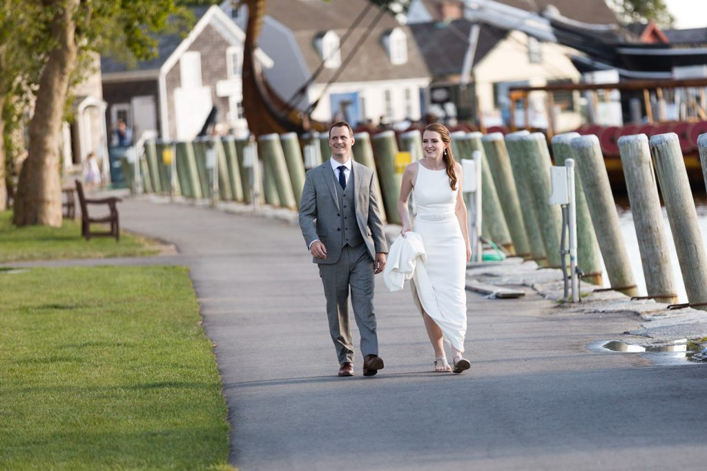 A bride and groom walk through mystic seaport to get to their wedding reception