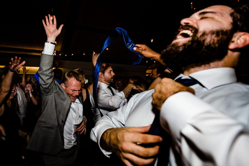 A man removes his tie while dancing at a Latitude 41 wedding