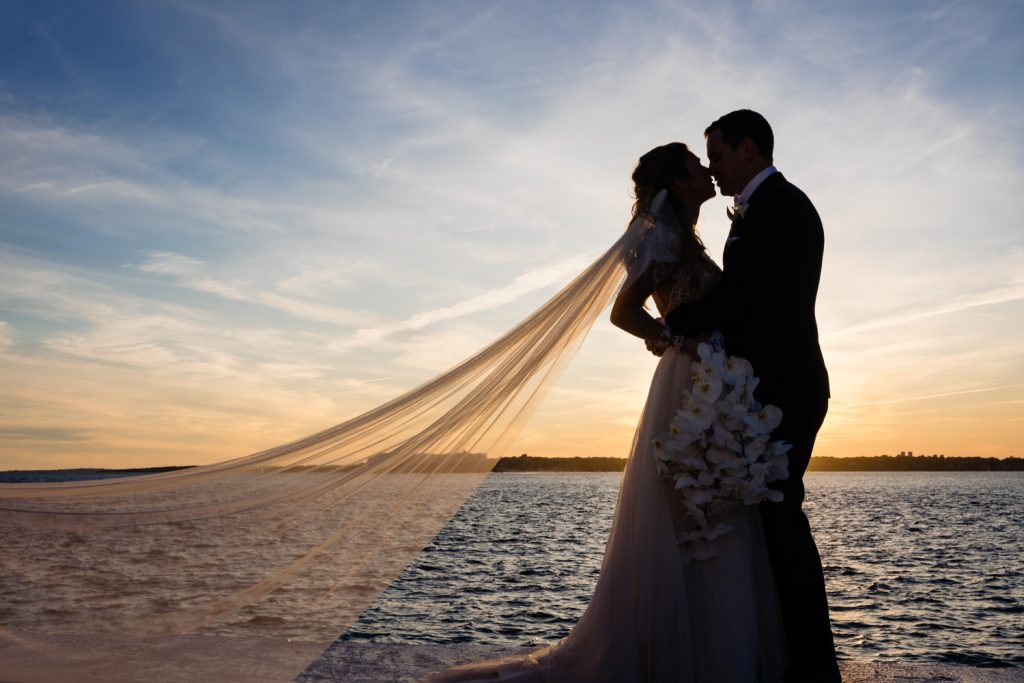 A bride and groom kiss at sunset on the sea wall at belle mer