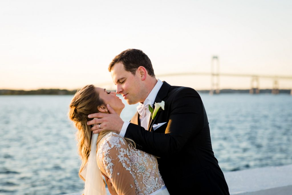 A bride and groom kiss at sunset in front of the newport bridge