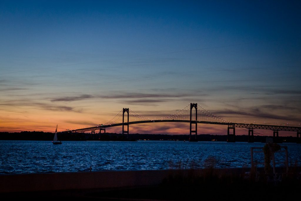 The view of a sunset over the newport bridge from belle mer