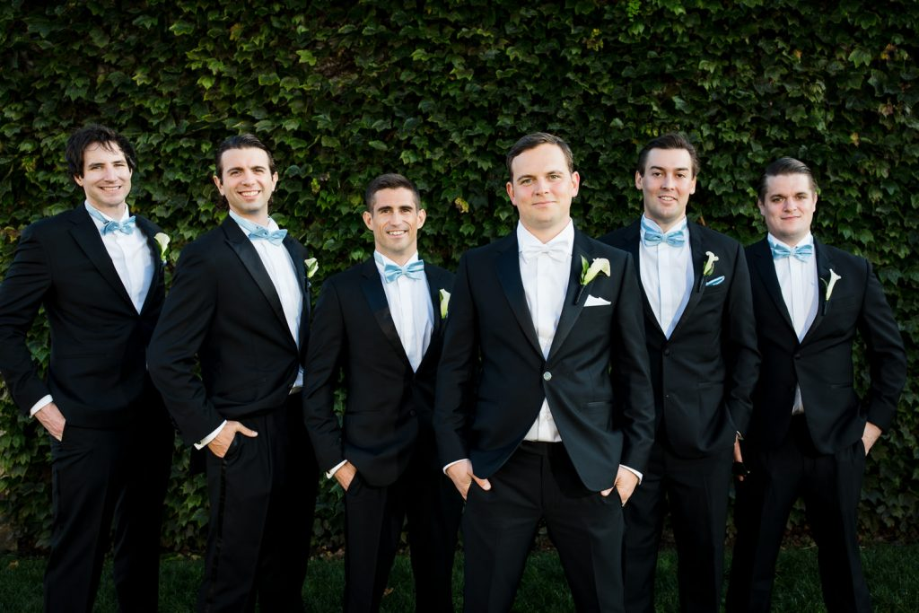 Groom and groomsmen pose in front of ivy wall at Belle Mer in newport ri