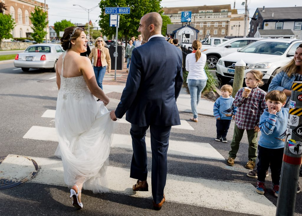 A bride and groom walk the streets of downtown newport ri to their wedding