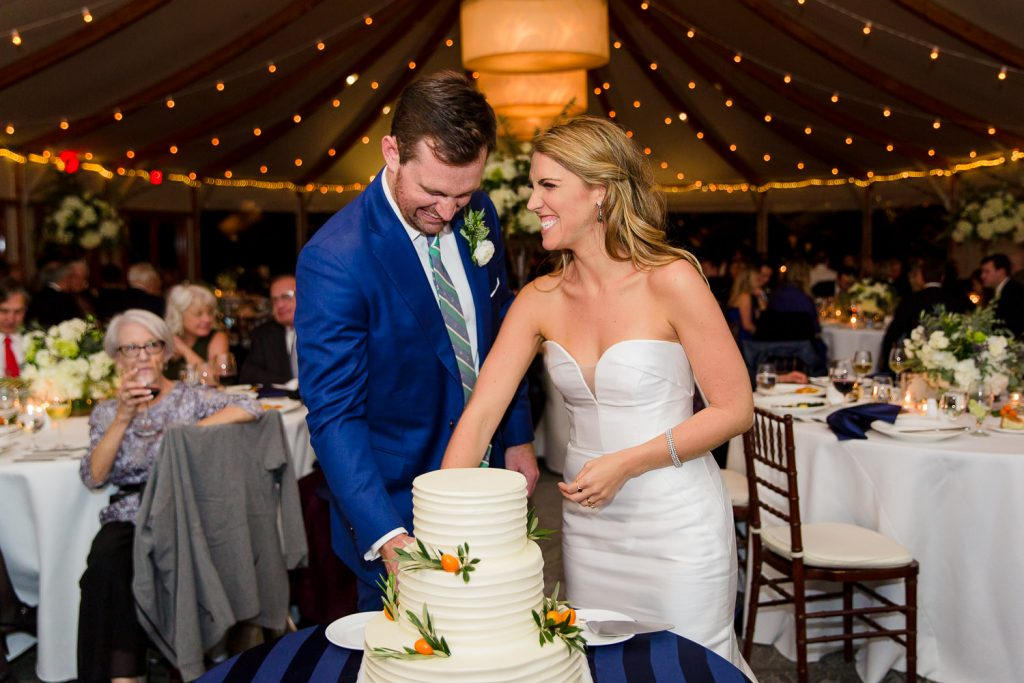 A bride and groom cut the cake under the tent at castle hill
