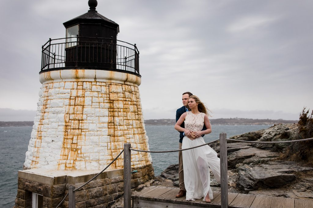 A couple embraces on the steps leading to the castle hill lighthouse in newport ri
