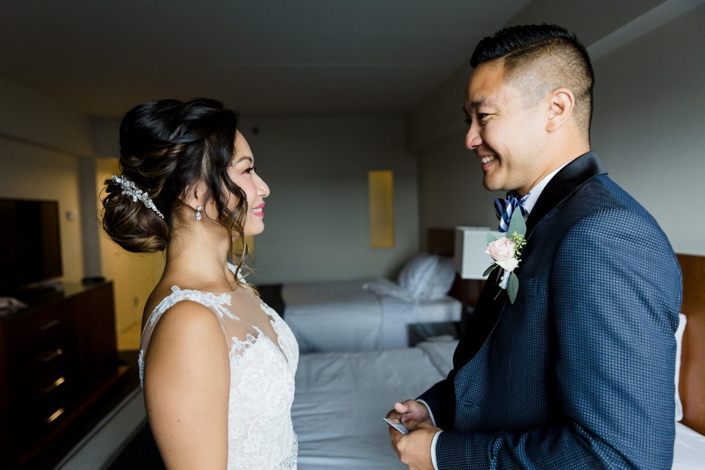 bride and groom have a first look in a hotel room at Gurney's newport resort