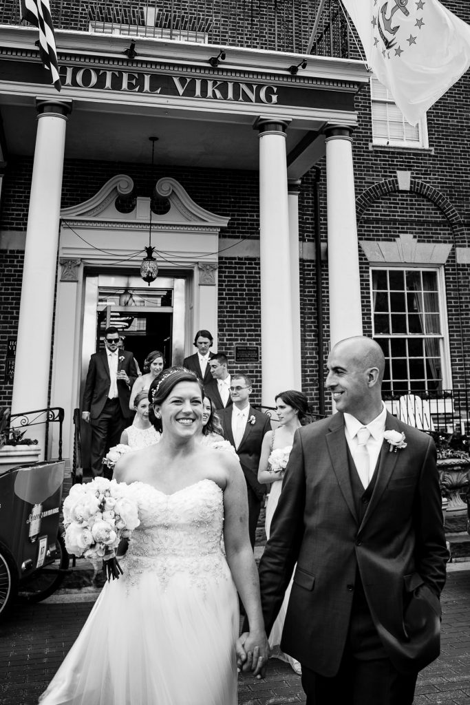A bride and groom walk out the front doors of the viking hotel in newport