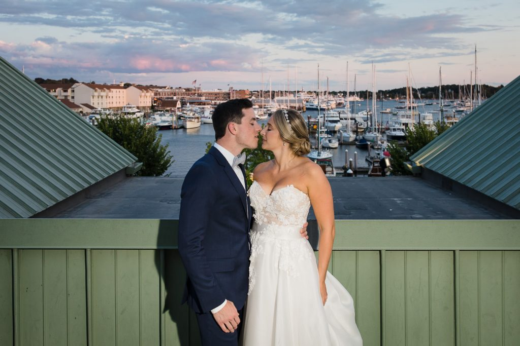 Bride and groom kiss on balcony at the Newport Marriott at sunset with boats in background
