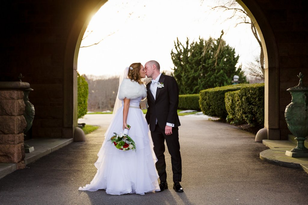 Bride and groom kiss under the archway at OceanCliff resort in newport ri