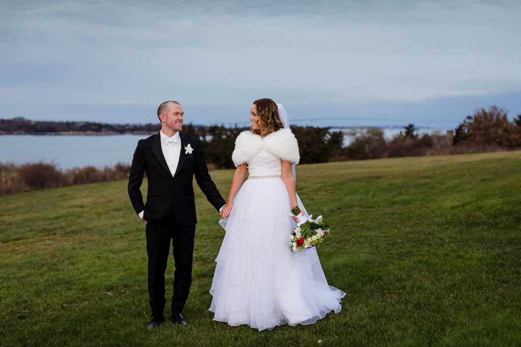 Bride and groom walk the manicured lawns at OceanCliff resort in newport