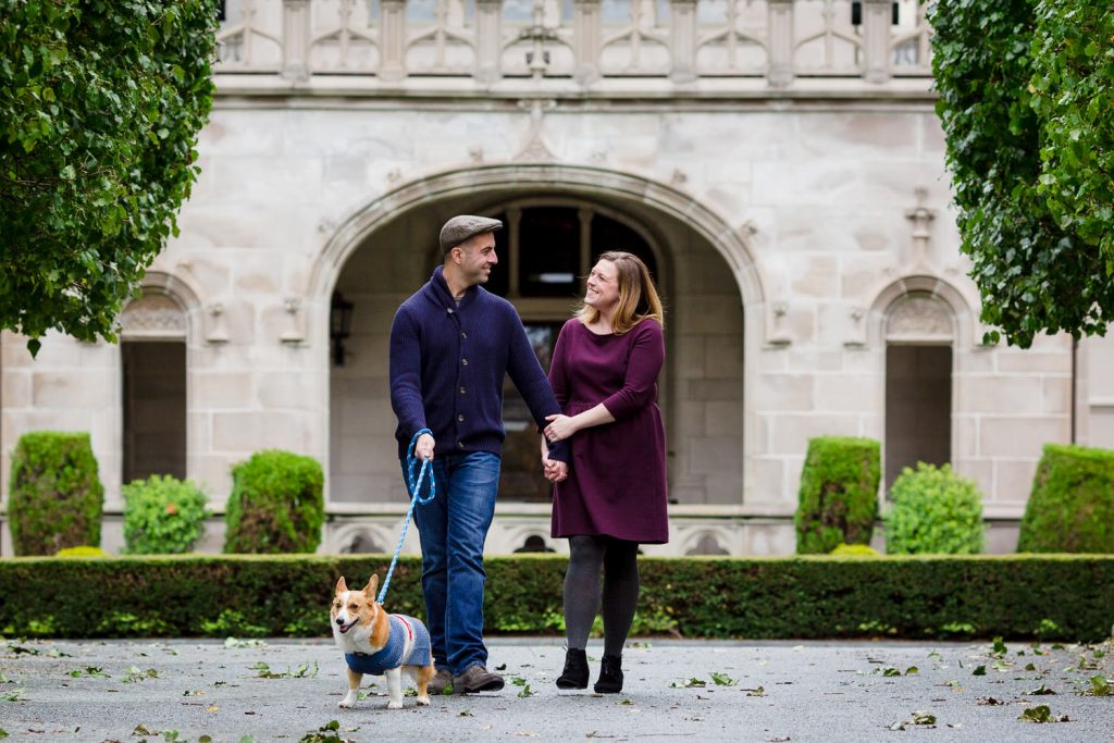 A couple and their corgi walk in front of ochre court mansion in newport ri