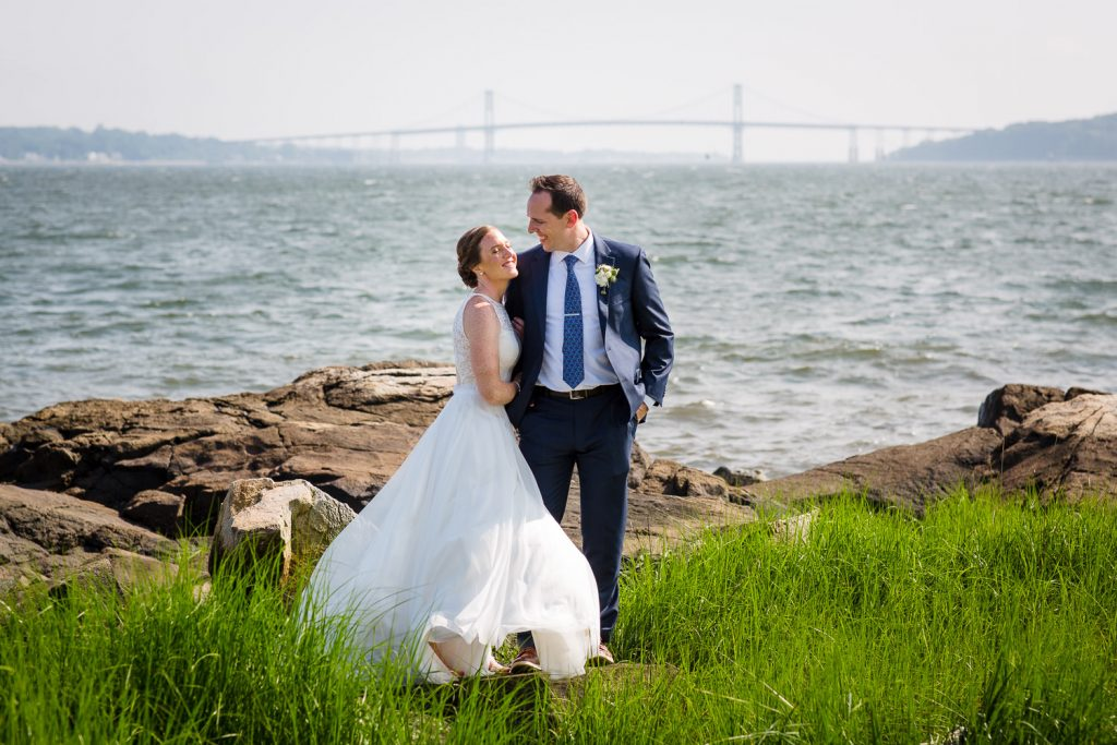 A bride and groom pose on the beach at mount hope farm