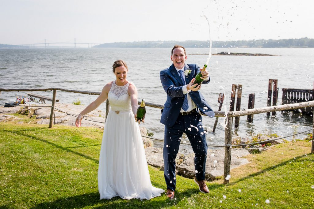 A bride and groom spray champagne at the cove cabin