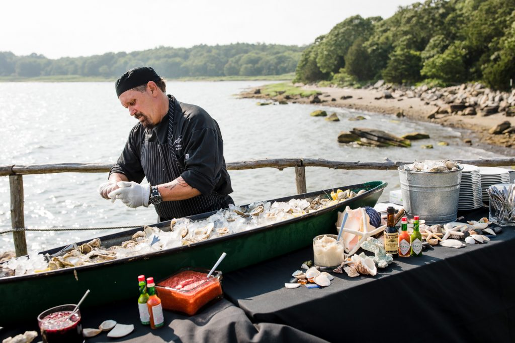 A server from morins catering shucks oysters at a raw bar at a mt hope farm wedding