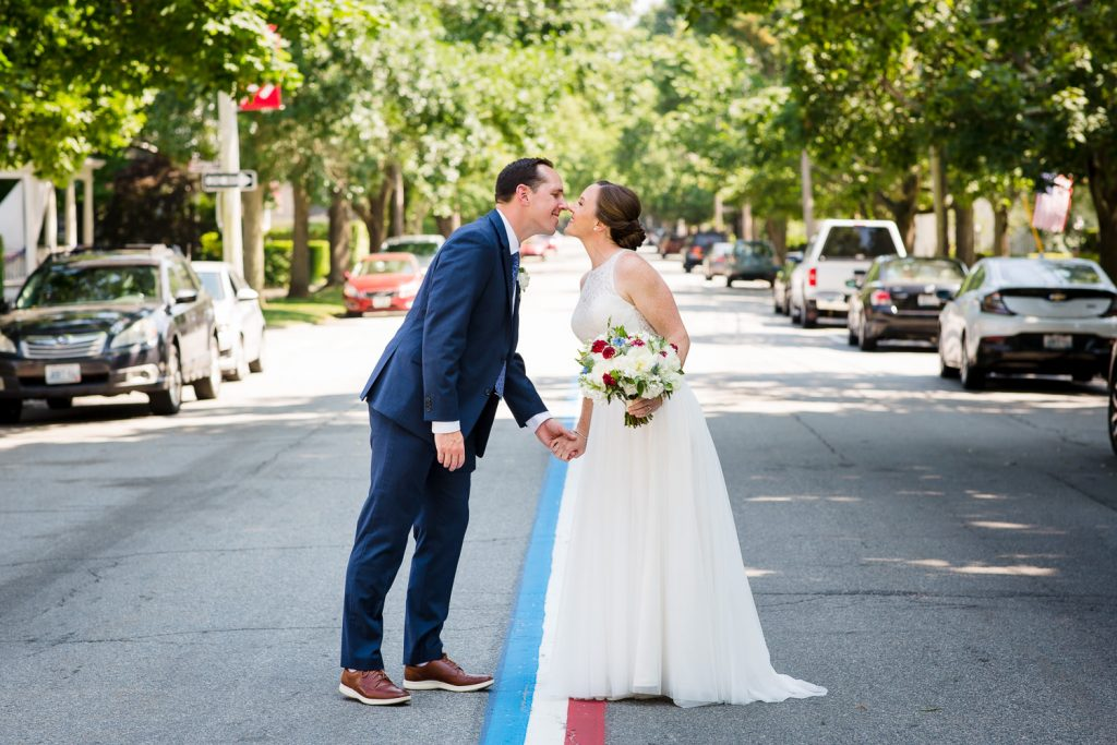 A bride and groom kiss along the fourth of july parade route in bristol ri