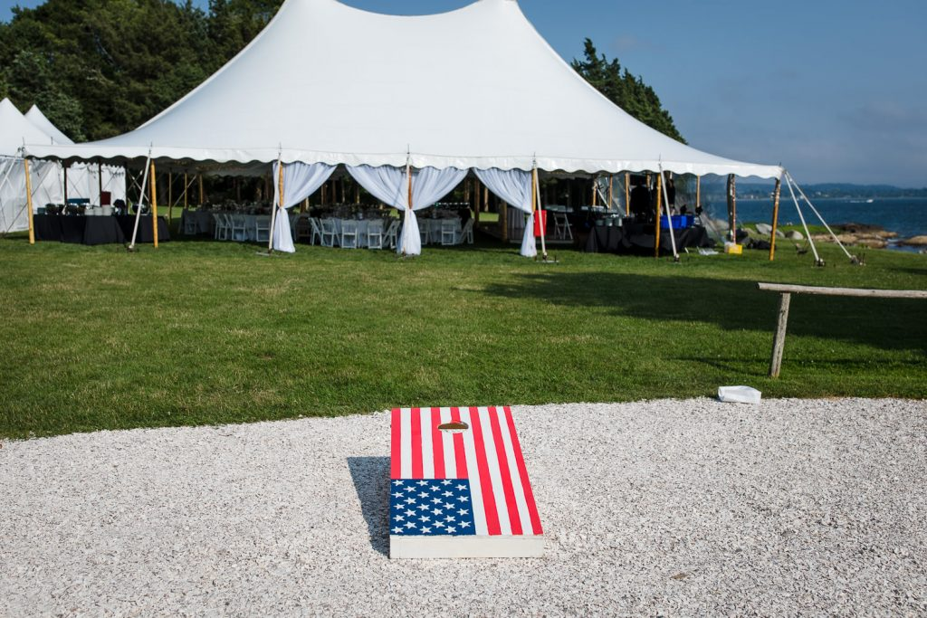 A cornhole set and white tent at a mount hope farm wedding