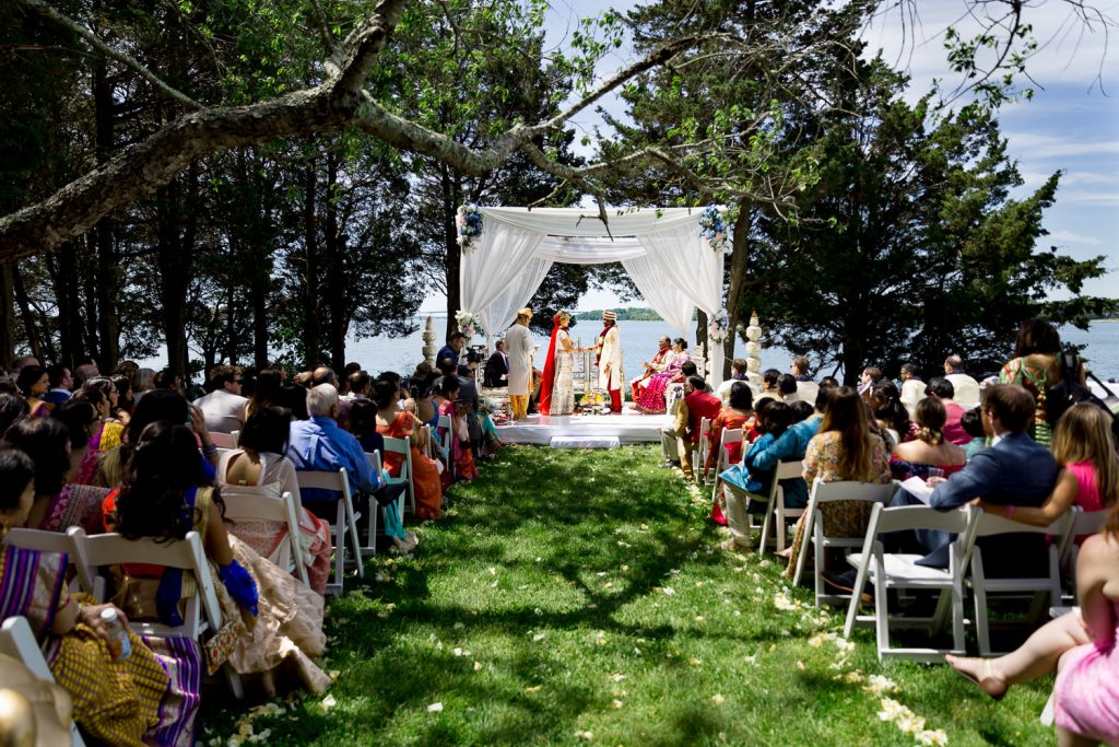 A traditional indian wedding ceremony on the lawn at mt hope farm cove cabin