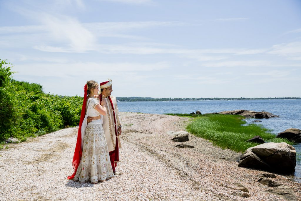 A bride and groom in traditional indian attire on the beach at mount hope farm