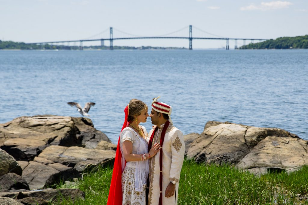 A bride and groom pose in front of the mt hope bridge at their rhode island indian wedding